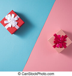 Valentine's Day celebration concept. A nice gift for your loved one. Boxes with bows on delicate blue and pink backgrounds. Copy space. Flat lay. Close-up.