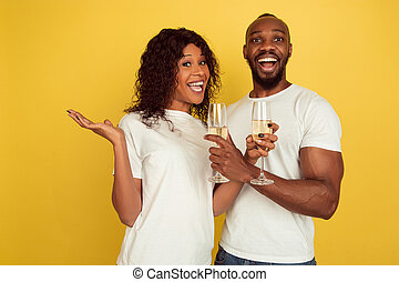 Valentine's day celebration, happy african-american couple isolated on yellow background