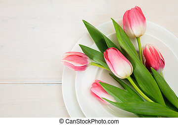Pink tulips on white plates, white wooden background. Top view