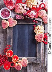 Valentines day cookies around a chalkboard