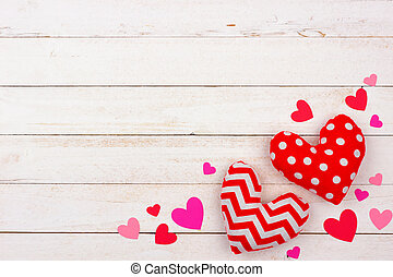 Valentines Day corner border of cloth pillow hearts against white wood