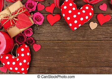 Valentines Day corner border of hearts, gifts, flowers and decor on rustic wood