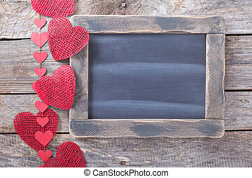 Valentines day decorations around a chalkboard copyspace