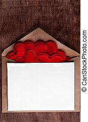 Valentine's day. Envelope with lots of red hearts and place for text .Brown wooden background.
