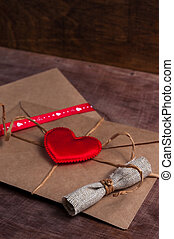 Valentine's day. Envelope with red hearts on Brown wooden background.