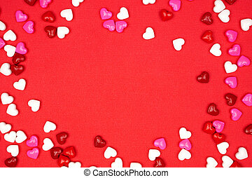 Valentines Day frame of candy hearts over a red background with copy space