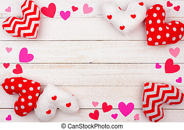 Valentines Day frame of cloth pillow hearts against white wood