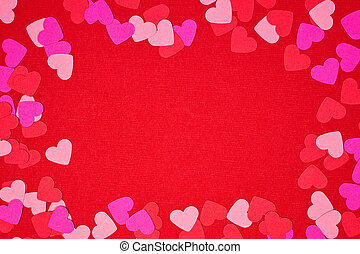 Valentines Day frame of heart confetti over a red background with copy space