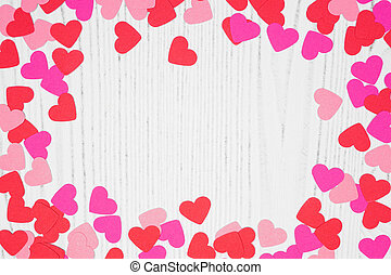 Valentines Day frame of heart confetti over a white wood background with copy space
