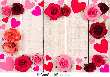Valentines Day frame of hearts and roses against rustic white wood