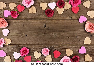 Valentines Day frame of hearts and roses against rustic wood