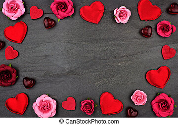 Valentines Day frame of hearts, flowers and decor against a dark background