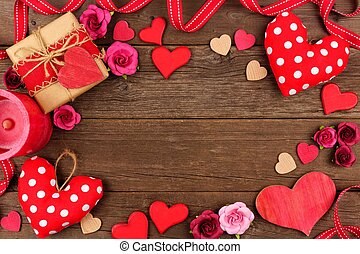 Valentines Day frame of hearts, gifts, flowers and decor on rustic wood
