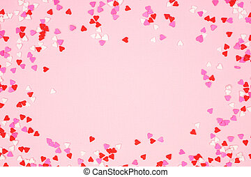 Valentines Day frame with candy heart sprinkles over a pink background with copy space