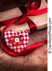 Valentine's day. Gift tied with ribbon and red heart on wooden background.