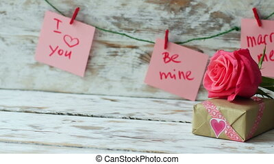 Valentines Day gift with pink rose on wooden background in vintage style. 4k dolly shot left to right