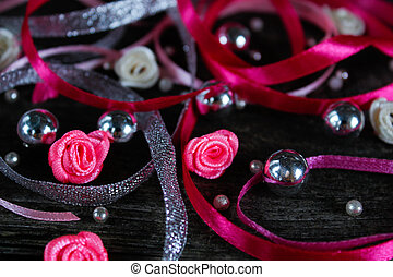 Valentine's day greeting card. pink ribbons, beads, hearts and little pink roses on a dark tree