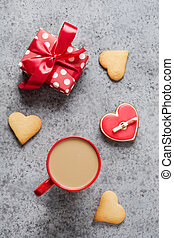 Valentines day greeting card with heart cookies, gift, coffee cup on grey table. Vertical.