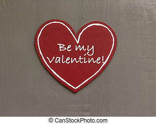 Valentines day greeting with red heart on wooden background