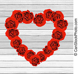 Valentines Day heart made of red roses on white wooden background