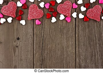 Valentines Day heart shaped candy top border on a rustic wood background