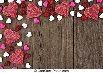 Valentines Day heart shaped candy top corner border on a rustic wood background