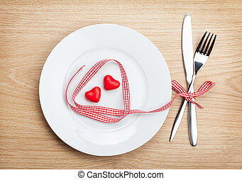 Valentine's Day heart shaped red ribbon over plate with silverware. On wooden table background