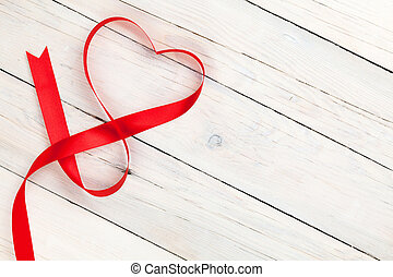 Valentines day heart shaped ribbon over white wooden table