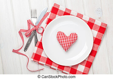 Valentines day heart shaped toy gift on plate with silverware