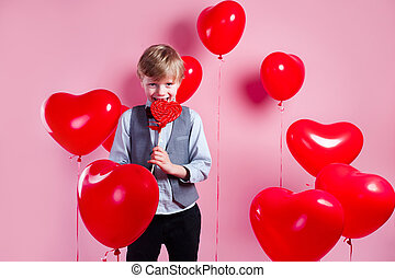 Valentines day. Little cute boy eating candy on red heart balloons background