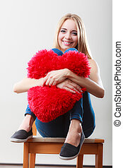 woman holding heart shaped pillow