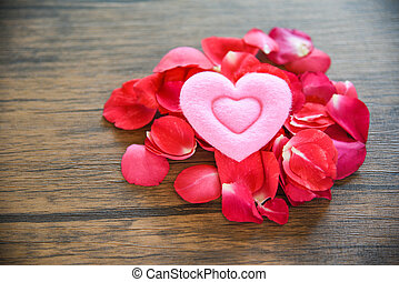 Valentines day love heart concept / Pile of roses petals with pink heart decorated on wooden table