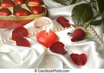 valentines day objects arranged with candle in the middle