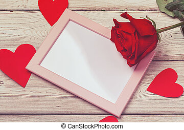 Valentines day photo frame or greeting card and handmaded hearts over table. Top view with copy space