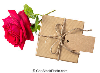 Rose red flower and a gift box with a blank tag on a white...
