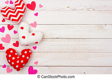Valentines Day side border of cloth pillow hearts against white wood