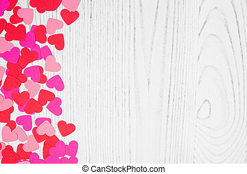 Valentines Day side border of heart confetti over a white wood background with copy space