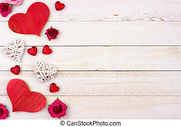Valentines Day side border of hearts, flowers and decor against white wood