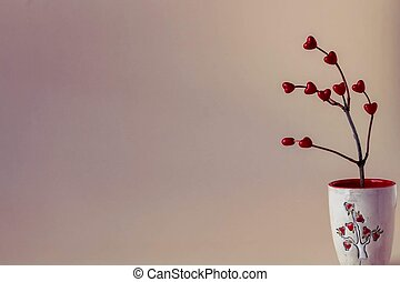 Valentine's day still life - dry branches in a ceramic vase with red hearts
