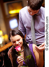 Valentine?s day - Image of pretty woman smelling rose and...