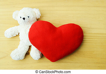 Valentines Day. Teddy Bear Loving cute with red heart pillow on wooden backgrounds above. Place for your text