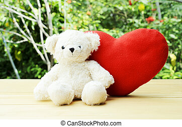 Valentines Day. Teddy bear with red heart sitting wooden board with green nature backgrounds