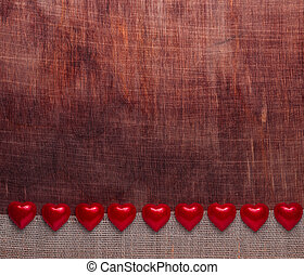 Valentine's day. The small hearts on a dark red wooden background.