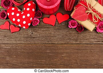 Valentines Day top border of hearts, gifts, flowers and decor on rustic wood