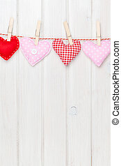 Valentines day toy hearts hanging on rope over white wooden...