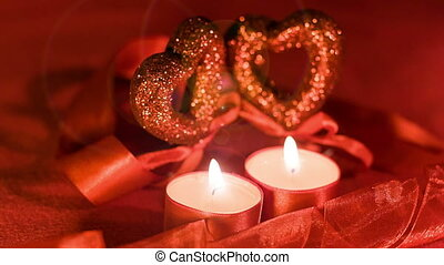 Valentines day, two candles burning in front of two hearts
