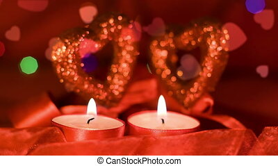 Valentines day, two candles burning in front of hearts