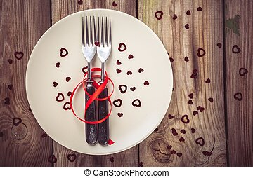 two forks on a plate with a red ribbon