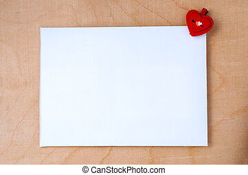 Valentine's day. White card with a small red heart on wooden background.