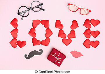 Valentine's day with red hearts gift lettering love party accessories on a pink background. Top view flat lay